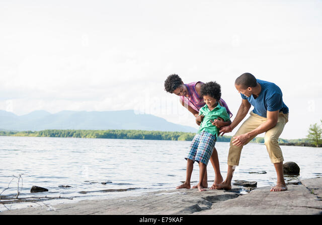 A family, mother, father and son playing on the shores of a lake. - Stock Image