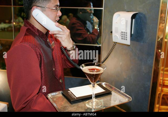 Puerto Rico Atlantic Ocean Holland America Line ms Noordam Lido Restaurant Asian male room service drink phone - Stock Image