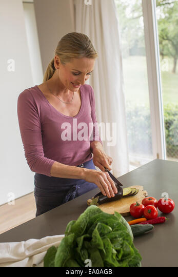 Mature woman slicing aubergine - Stock Image