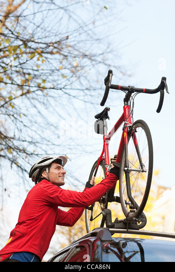 Mid adult man lifting bicycle onto car roof rack - Stock Image