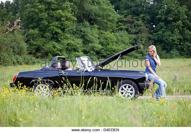 A young woman sitting on her broken down car speaking on a mobile phone - Stock Image