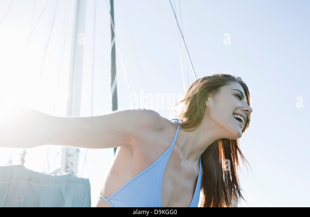 Young brunette woman on yacht, laughing - Stock-Bilder
