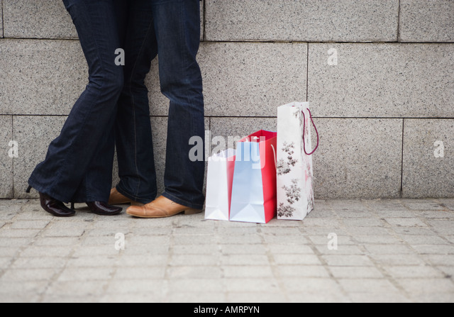 Couple hugging on urban street with shopping bags - Stock-Bilder