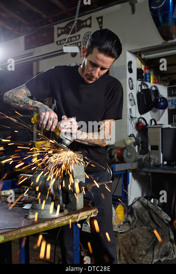 Mature man welding parts in motorcycle repair workshop - Stock Image