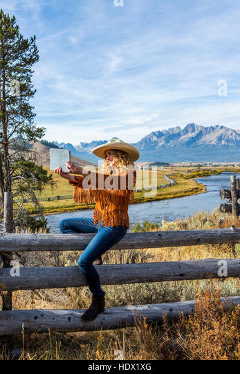 Caucasian woman sitting on wooden fence posing for selfie - Stock Image