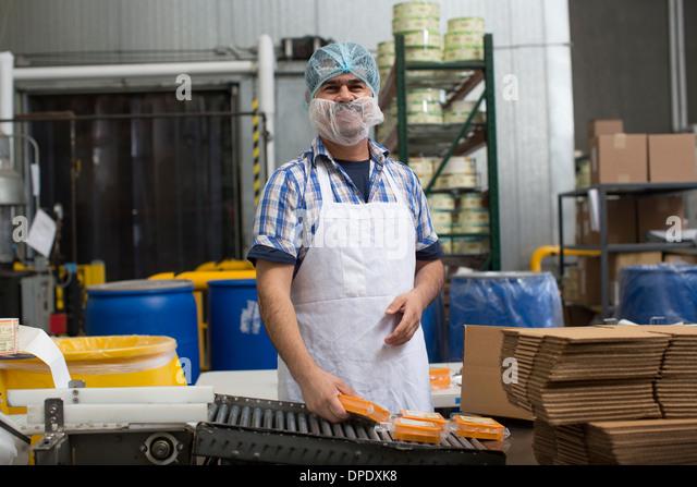 Man packaging vegan cheese in warehouse - Stock Image
