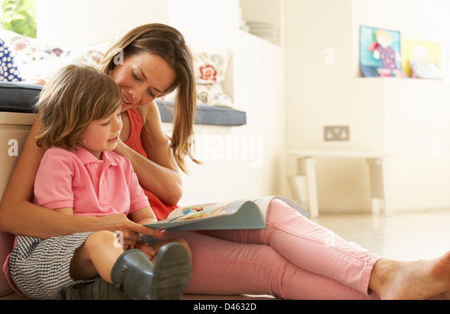 Mother Sitting With Son Reading Story Indoors - Stock Image