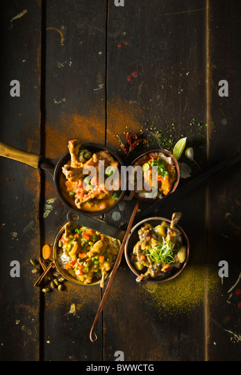 Four Ethnic Chicken Stews inside four different rustic vessels on a rustic wood table. From Top left clockwise: - Stock Image