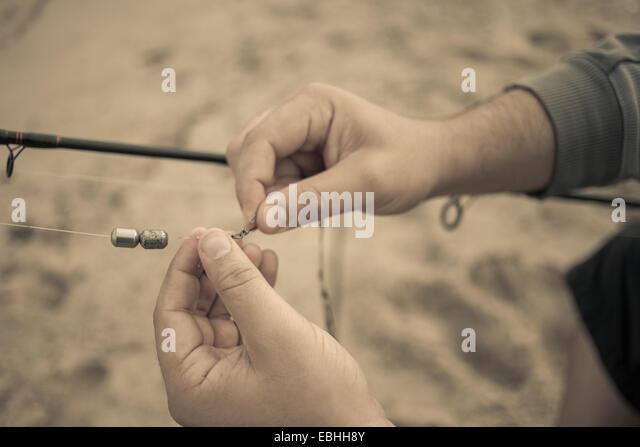 Close up of fishermans hands preparing fishing rod, Truro, Massachusetts, Cape Cod, USA - Stock Image