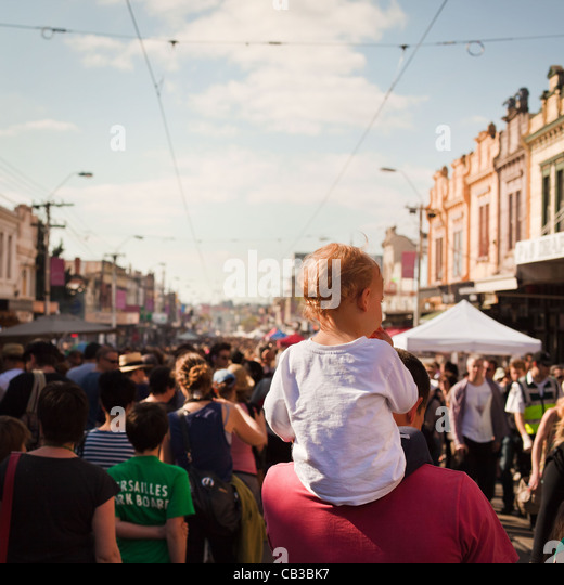 High Noon community festival is a Northcote local music fest in Melbourne, Australia child gets a piggy back through - Stock Image