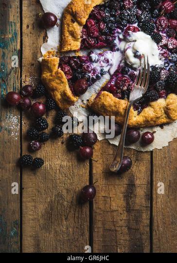 Garden berry galetta sweet pie with melted vanilla ice-cream scoop - Stock Image