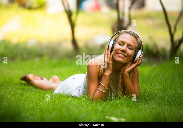 Happiness emotional girl with headphones enjoying nature and music at sunny day. - Stock Image