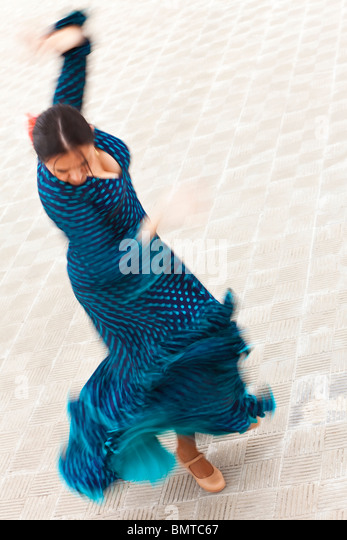 A motion blurred slow shutter speed shot of a woman traditional Spanish Flamenco dancer dancing in a blue polka - Stock Image