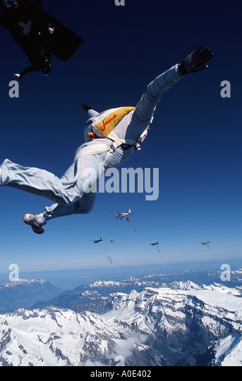 Skydivers exit a multi airplane formation above the swiss alps - Stock Image