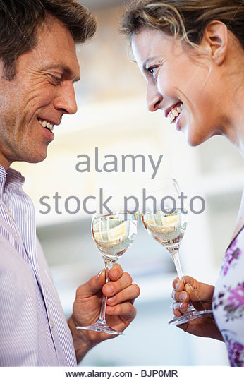 Couple clinking glasses of white wine - Stock Image