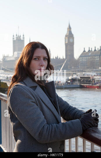 An attractive woman with long dark hair looks to camera with Big Ben and other London landmarks in the background - Stock Image