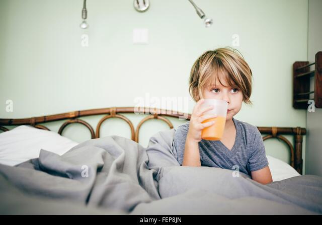 Boy sitting in bed drinking beaker of orange juice, looking away, Bludenz, Vorarlberg, Austria - Stock Image