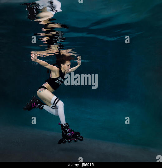Young woman roller blading underwater, Virginia Beach, VA - Stock Image