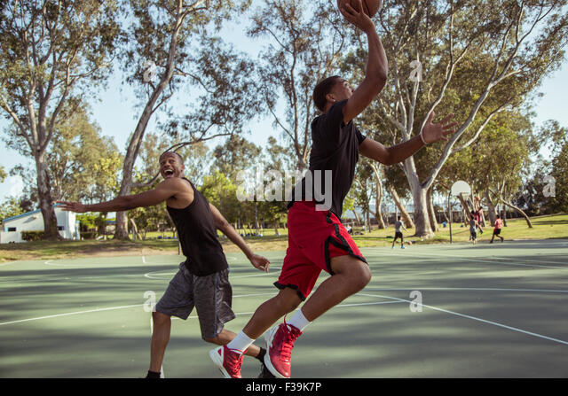 Two young men playing basketball, shooting hoops in the park at sunset - Stock Image