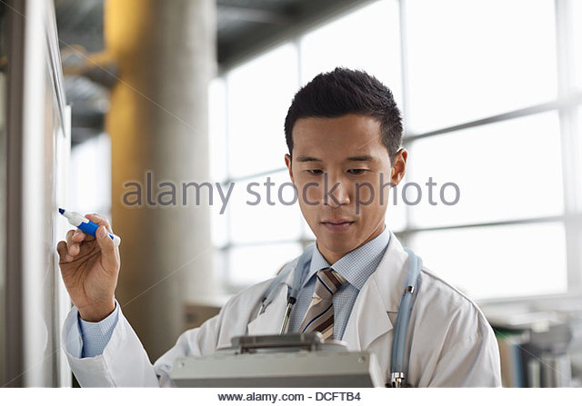 Male doctor copying notes from clipboard - Stock Image