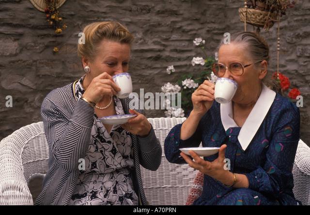 two elderly women drinking tea - Stock Image