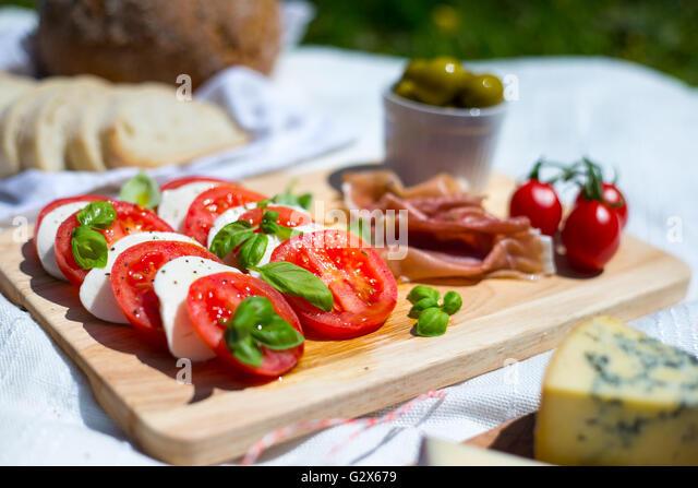 A picnic of tomato and mozzarella salad, parma ham, strawberries, olives and espresso pot in a park - Stock Image