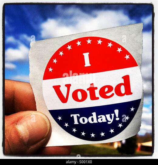 Hand holding an 'I voted today'sticker against clouds in the sky - Stock Image