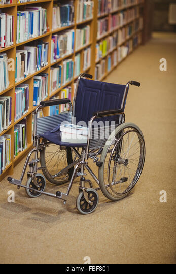 Wheelchair with books in bookshelves - Stock Image
