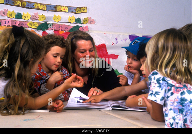 GROUP OF CHILDREN SEATED AROUND TABLE WITH TEACHER IN KINDERGARTEN - Stock Image