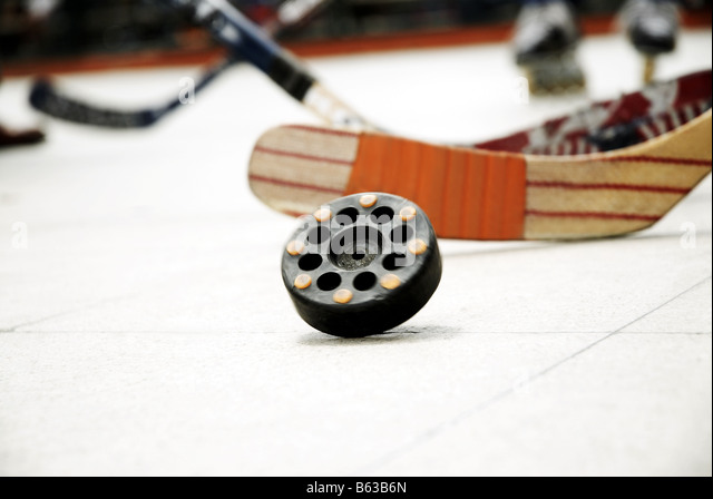 Close-up of a hockey puck with an ice hockey stick - Stock Image