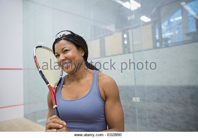 Smiling woman holding squash racket - Stock Image
