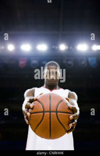 Basketball player holding basketball, focus on foreground - Stock Image