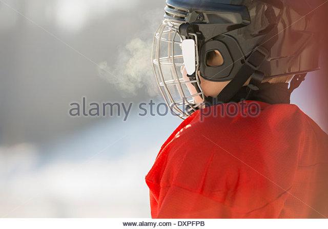 Side view of boy in ice hockey helmet - Stock Image