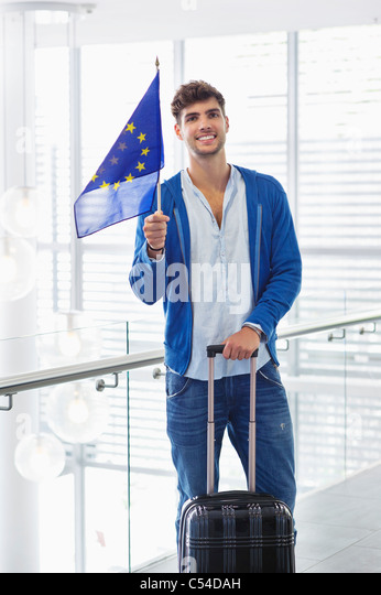 Portrait of a man holding European union flag and a suitcase at an airport - Stock Image