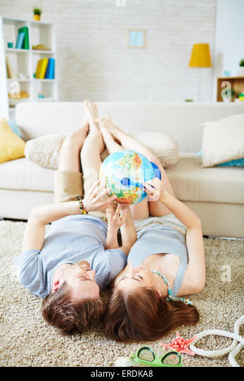 Restful couple with globe lying on the floor by sofa at home - Stock Image