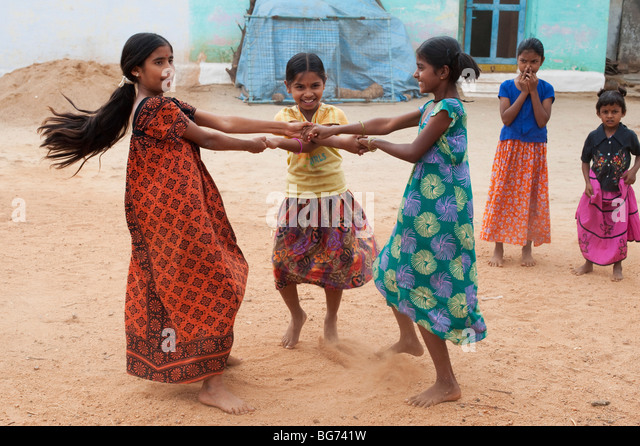 Indian girls swinging around in their village. Andhra Pradesh, India - Stock Image