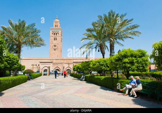 Tourists sitting in the gardens next to the Koutoubia Mosque, Marrakech (Marrakesh), Morocco, North Africa, Africa - Stock Image