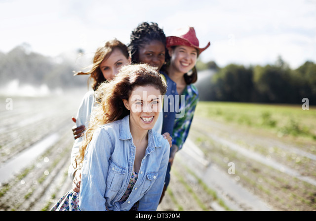 Four young women in a field full of seedlings an organic crop with sprinklers spraying water in the background - Stock Image