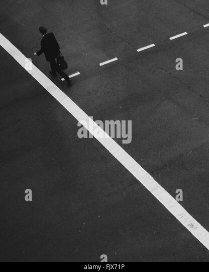 High Angle View Of Man Walking On Road - Stock Image