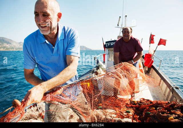 Fisherman pulling in nets - Stock Image