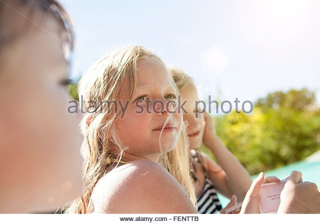Three young children, outdoors, looking away - Stock Image