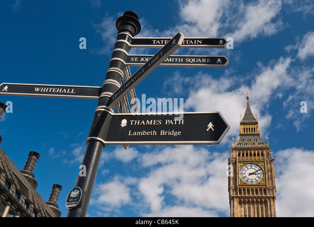Sign post in Westminster directing visitors to various points of interest Big Ben in background London UK - Stock Image