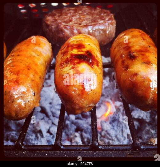 Three sausages and a burger cooking on a barbecue - Stock Image