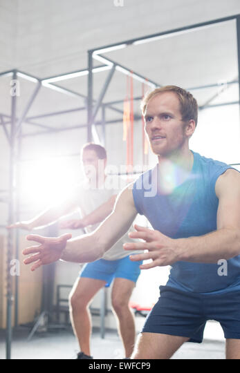 Determined men exercising at crossfit gym - Stock Image