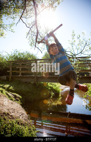 Boy swinging on a rope - Stock Image
