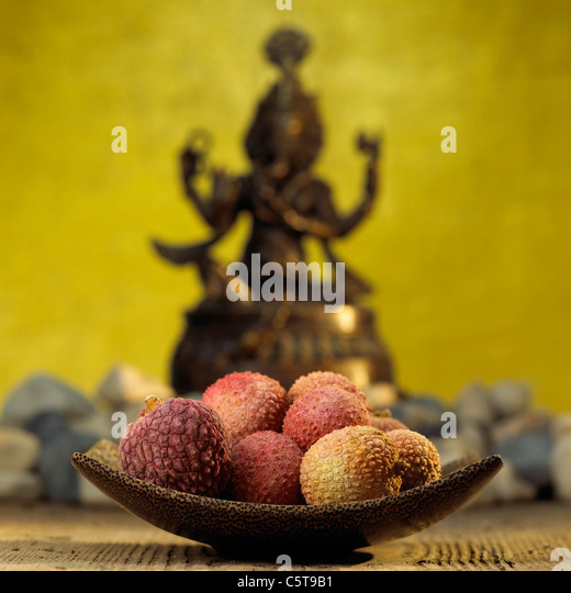 Litchi fruits on wooden bowl - Stock Image