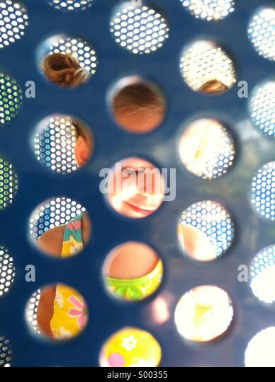 A young girl seen thru a playground partition - Stock Image
