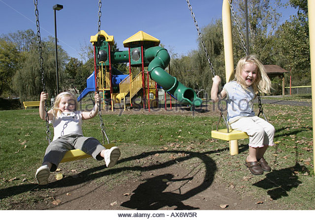 West Virginia Ronceverte playground girls twins swings - Stock Image