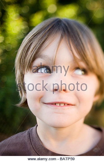 Boy smiling outdoors - Stock Image