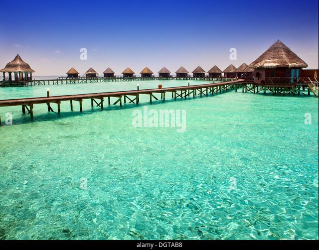 Island in ocean, overwater villas - Stock Image